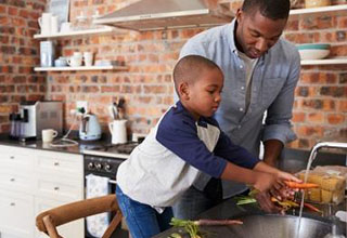 Son Helping Father To Prepare Vegetables For Meal In Kitchen - Image