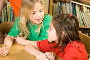 Girls sat at school table talking