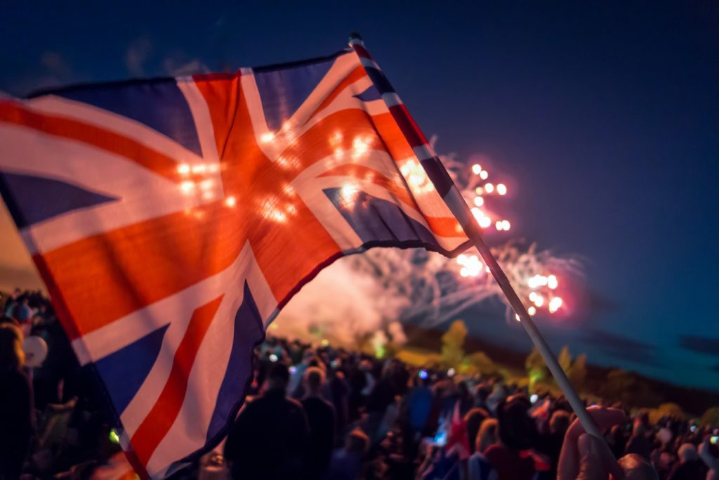 A Union Jack flag waves above a crowd watching a firework display