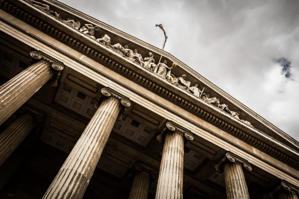 A Union Jack flaps in the wind above the portico of the British Museum