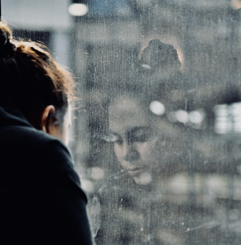 A child's contemplative expression is seen reflected in a window