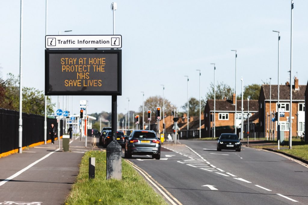 An illuminated road sign reads 'stay home, protect the NHS, save lives'