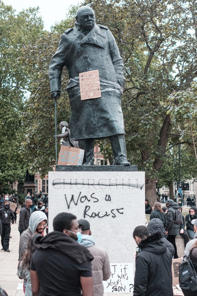 A demonstration around a statue of Winston Churchill, underneath whose name has been written 'was a racist'