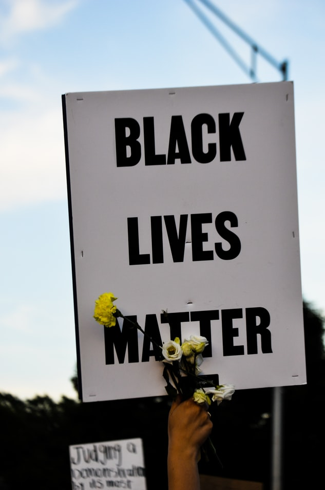 A demonstrator holds up a Black Lives Matter sign, along with some flowers