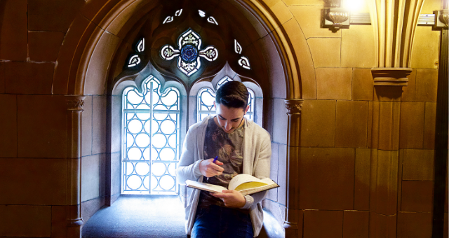 Student reading book in front of library window