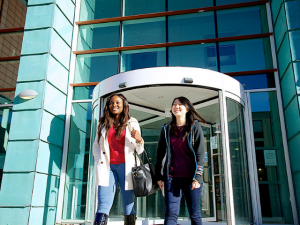 Two female students leaving university building smiling