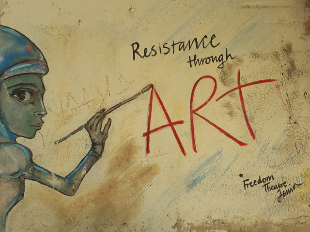Graffiti of a person painting 'resistance is art' on a wall