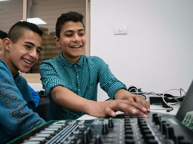 Palestinian boys enjoying learning how to use music studio equipment